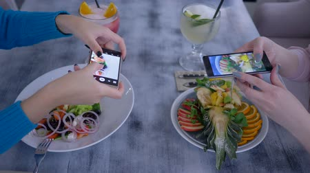 dietético : vegetarians girls taking photo of delicious eating on cell phone for social networks during healthy lunch in restaurant close up Stock Footage