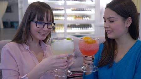 dietético : tasty diet, beautiful happy girls communicate and drinking juice through a straw from large glasses inside restaurant Stock Footage