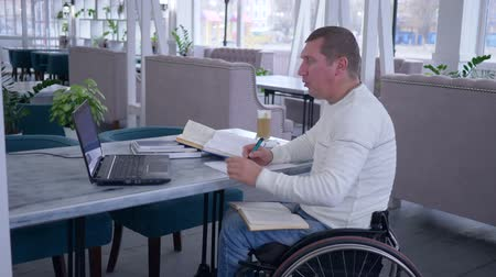 diseased : successful diseased student man on wheel chair works on laptop computer during distance learning for online education and makes notes in notebook in restaurant Stock Footage