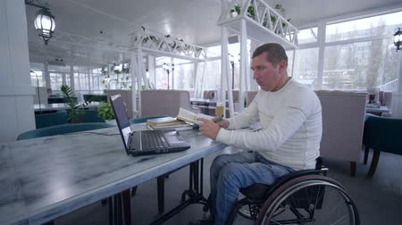 correspondência : online education of handicapped, student disabled man on wheelchair uses modern laptop technology to learn from online lessons and books making notes in notebook close-up sitting at table in cafe Stock Footage