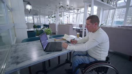 levelezés : online education, successful student invalid men on wheelchair uses modern laptop technology to learn from online teaching and books making notes in notebook close-up sitting at table in cafe