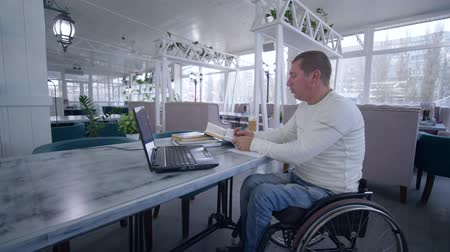 lecture : successful student crippled man on wheelchair using laptop computer for video education to learn from online teaching making notes in notebook in cafe