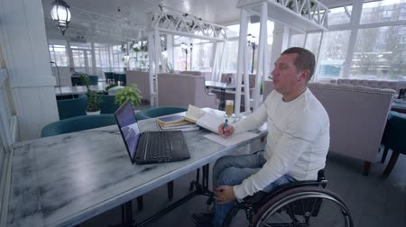 inwalida : Successful invalid restaurant owner man on wheelchair uses modern computer technology for management and development business ideas indoors