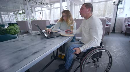 inwalida : education courses for disabled, Smart aching student mature men in wheelchair with tutor female during home education using modern computer technology in restaurant