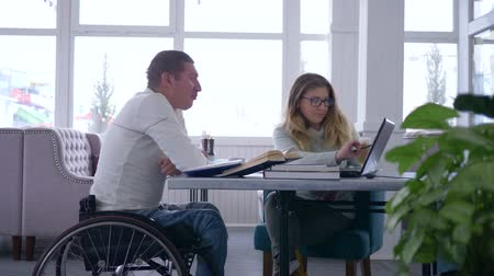 diseased : education for handicapped, diseased student senior man in wheelchair with tutor women during home teaching courses using laptop computer in restaurant