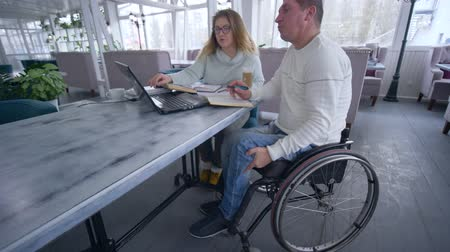 репетитор : freelance businessman is disabled on wheelchair with woman using smart computer technology for developing and planning business ideas in restaurant Стоковые видеозаписи