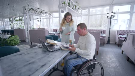 inwalida : freelance lifestyle of invalid, Creative disabled man on wheelchair with female with cup coffee working on laptop computer for planning and managing business and develop ideas Wideo
