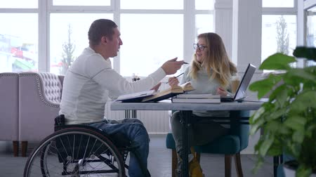 diseased : individual studying for disabled, teacher woman into eyeglasses conducts lecture for invalid male on wheelchair using a laptop computer and books in cafe