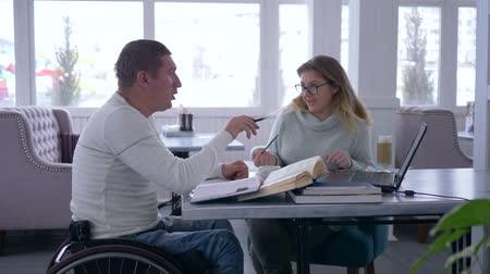 lecture : individual training for disabled, smart teacher female into glasses provides teaching for invalid man on wheelchair using modern computer technology and books in cafe