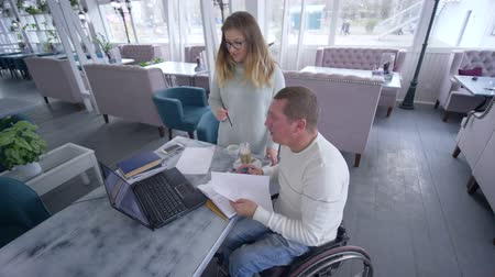 diseased : professional education of handicapped mature male in wheelchair with teacher women using smart computer technology during personal lesson in cafe Stock Footage
