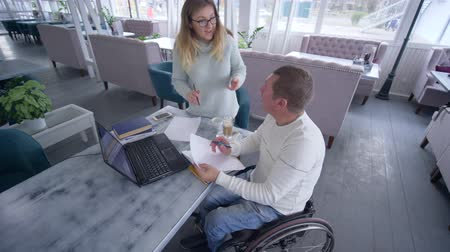 inwalida : tutoring for disabled, successful crippled man in wheelchair with educator woman using smart computer technology during personal lesson in cafe