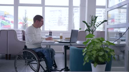 переписка : developing of Disabled mature man in wheelchair into glasses works on laptop during distance online learning sitting at table in cafe