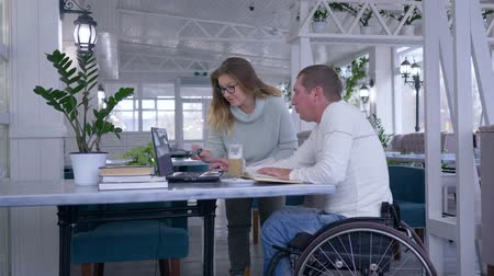 diseased : successful disabled, creative freelance businessman in wheelchair With woman discuss startup business using laptop computer in cafe