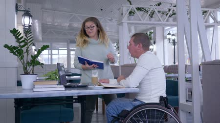 diseased : training for invalid, happy sick student mature men in wheelchair with educator female using smart computer technology during personal lecture indoors