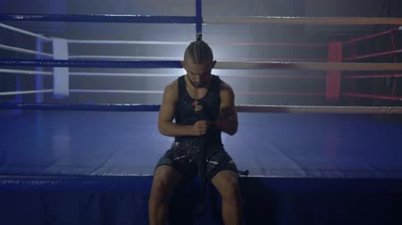 worstelaar : sport attractive boxer tuned to fight and reel up black bandages for Kickboxing sitting near ring at semi-darkness