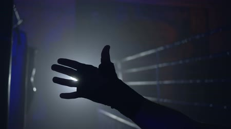 worstelaar : dark figure of boxer hand against of ring in backlight in dark close-up Stockvideo