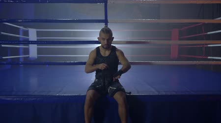 worstelaar : sport preparation, muscular wrestler reel up black bandages for boxing before fight sitting near ring at semi-darkness