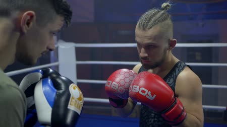 worstelaar : KHERSON, UKRAINE - OCTOBER 10, 2018: boxing match in professional sport, wrestlers guys fight with fists in boxing gloves while sparring in ring at competitions close-up, slow motion