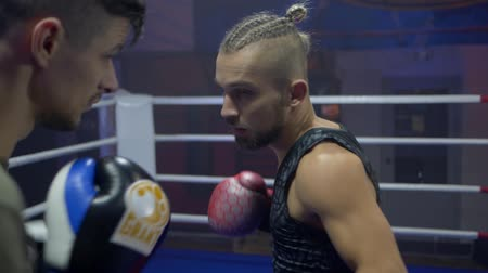 zapasy : KHERSON, UKRAINE - OCTOBER 10, 2018: professional boxing, sportsman fight with fists in boxing gloves while sparring in ring at contest close-up, slow motion
