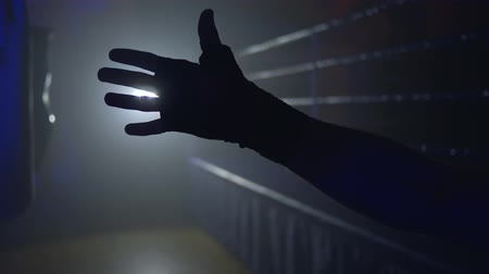 worstelaar : silhouette of hand fighter against of ring in backlight in dark close-up
