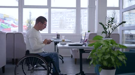 inwalida : business freelance, senior man crippled in wheelchair wearing glasses uses a mobile phone and working on a laptop sitting at a table in a cafe