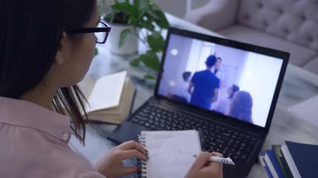 netbook : electronic training, girl student in eyeglasses with pen writes in notepad during watching a video on a notebook Stock Footage