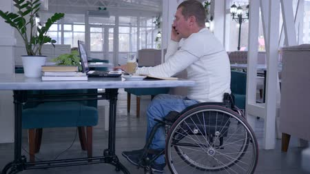 deficientes : handicapped man in wheel chair talking on a mobile phone and working with a computer laptop sitting at a table with cup of coffee in a restaurant.