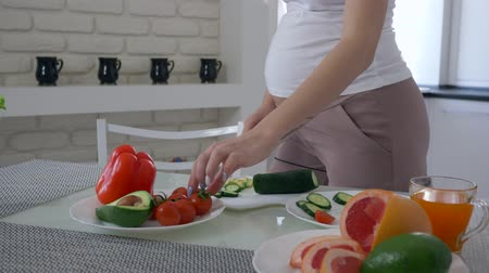 abobrinha : healthy food during pregnancy, future mother with big belly is cooking useful appetizing eating for breakfast from fresh vegetables at kitchen