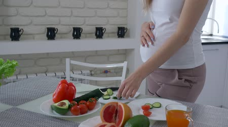 abobrinha : healthy lifestyle of pregnant female with big tummy is cooking useful delicious food for dinner from fresh vegetables at kitchen close-up