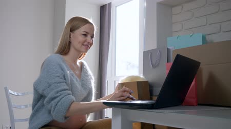 fertility : online communication, happy pregnant girl with bare tummy Shows new purchases in shopping packages while chatting with friends on Internet sitting in front of laptop at home Stock Footage