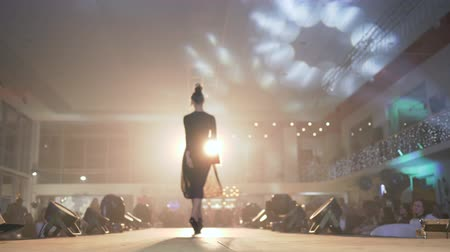searchlight : KHERSON, UKRAINE - DECEMBER 01, 2018: Catwalk model female into high heels shoes into black fashionable dress walks on podium at bright spotlight in front of viewer people at unfocused