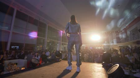 podium : KHERSON, UKRAINE - DECEMBER 01, 2018: Defile show, model podium in sneakers and silver stylish suit of designer collection walks on catwalk in spotlights before spectators at fashion show