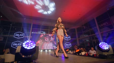 néző : KHERSON, UKRAINE - DECEMBER 01, 2018: fashion evening, leggy catwalk model in high heels shoes into designer garments presents new collection into searchlight Stock mozgókép