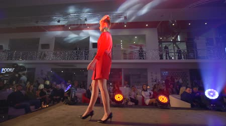 semana : KHERSON, UKRAINE - DECEMBER 01, 2018: fashion show, model girl into beautiful red dress in high heels shoes walks down podium into spotlights Stock Footage
