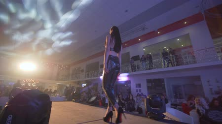 floodlight : KHERSON, UKRAINE - DECEMBER 01, 2018: fashion Week, young model female in high heels in shiny suit of new collection walks on catwalk in searchlight before audience at Defile show