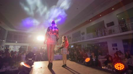 néző : KHERSON, UKRAINE - DECEMBER 01, 2018: fashionable model podium with little girl go on runway on presentation family clothing collection at fashion show Stock mozgókép