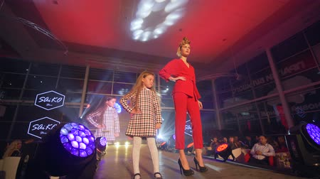high heeled shoe : KHERSON, UKRAINE - DECEMBER 01, 2018: trendy model girl with child make defile at presentation of new collection of designer clothes at fashion Week
