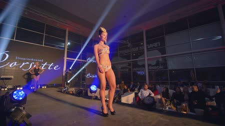 diváků : KHERSON, UKRAINE - DECEMBER 01, 2018: fashion event, catwalk model into bikini with beautiful figure walks on runway at presentation of new collection swimsuits in bright light searchlight