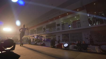nézők : KHERSON, UKRAINE - DECEMBER 01, 2018: fashion show, podium model girl into swimsuit walks on catwalk at presentation of new collection in bright light spotlight
