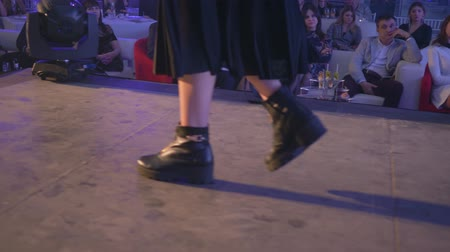 semana : KHERSON, UKRAINE - DECEMBER 01, 2018: fashion event, legs of model in stylish boots walks up catwalk at presentation of new designer collection into floodlight
