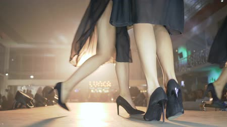 high heeled shoe : KHERSON, UKRAINE - DECEMBER 01, 2018: fashion show, beautiful legs in black high-heeled shoes take turns at podium at presentation of new designer collection into floodlight