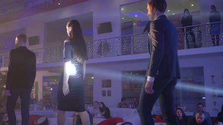 high heeled shoe : KHERSON, UKRAINE - DECEMBER 01, 2018: fashion show, professional models guys and girls in elegant dresses and suits go on catwalk in row after defile at presentation of designer clothes