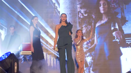 floodlight : KHERSON, UKRAINE - DECEMBER 01, 2018: professional models podium into new clothing walks down runway during show of new designer collection of clothes at fashion event Stock Footage