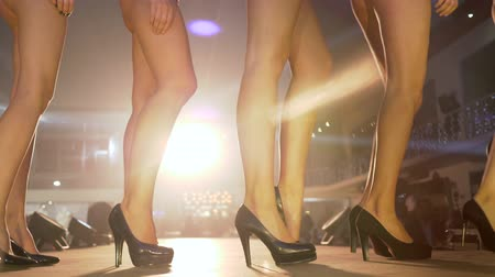 gösterileri : KHERSON, UKRAINE - DECEMBER 01, 2018: slender legs of models in high-heeled shoes go in row on catwalk close-up in spotlight lighting at fashion event