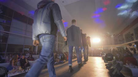 néző : KHERSON, UKRAINE - DECEMBER 01, 2018: trendy men models in stylish designer clothes of new collection go on catwalk at fashion show in front of audience at spotlights