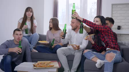sorte : home party, company youth friends eat pizza and drink beer while watching television sitting on sofa in room at holiday