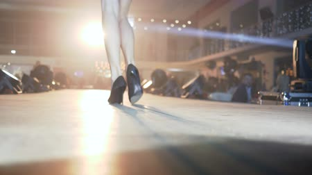 high heeled shoe : Defile show, leggy model woman in designer swimwear On high heels walks on catwalk in spotlights out of focus at presentation of new collection Stock Footage