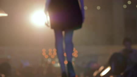 semana de moda : fashion evening event, silhouette catwalk model into gown walk on podium in backlight in unfocused during presentation of new collection clothes Stock Footage