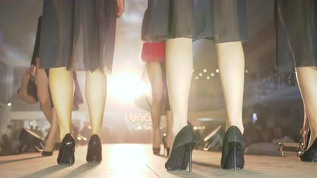 semana de moda : fashion evening, slender legs of models in black high-heeled shoes walk on podium in bright light close-up on unfocused background during presentation of new collection clothes