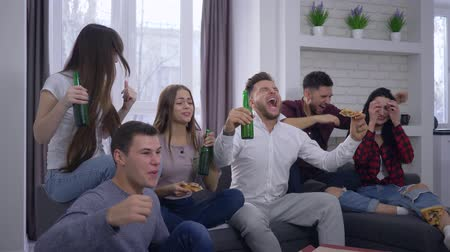 schreeuwen : emotion, fans watching football match on TV with excitement and then rejoice at the victory sitting on the couch with a beverages and pizza at home